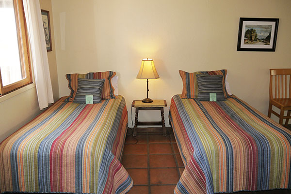 Two single beds in large bedroom in the Guest House