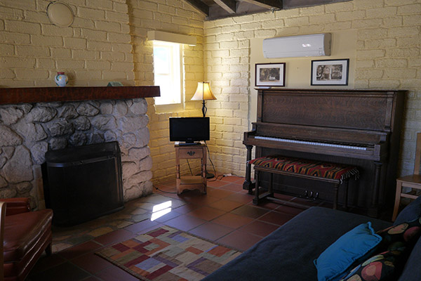 Family room with fireplace and piano West End Cottage