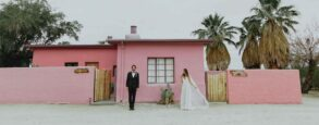 A couple standing in front of a pink adobe