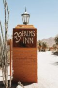 A sign at the front of 29 Palms with a desert landscape in the background