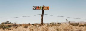 A desert landscape with a sign that reads