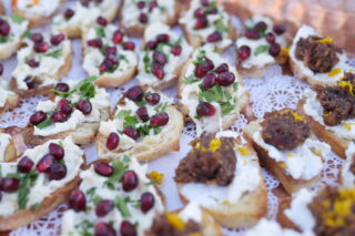 plate of crostini appetizers with cheese and pomegranate