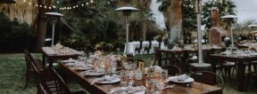 Long tables with table-settings on the lawn at 29 Palms, string lights are in the background