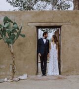 A bride and groom standing in an open doorway of and adobe structure, cacti are visible on the left