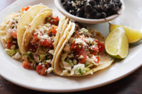 Plate of tacos with bowl of black beans
